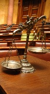 Close up image of justice scales sitting on a table inside a court room.
