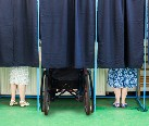 Image of three voting booths with cutains closed. The feet of two people can be seen below the curtain. One of the people voting is in a wheel chair.