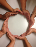 Photo of eight hands forming a circle.