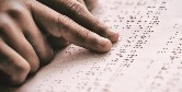 Close up photo of a man's hands reading a braille document.
