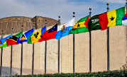 Photo of many flag poles with different nations flags in front of UN building.