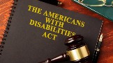 A close up image of a binder with a judges gavel resting on top of it. The cover of the binder says The Americans With Disabilites Act.
