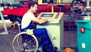 A man in a industrial plant operating machinery. He has a disablity and is in a wheel chair.