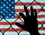 An image of a hand grabbing a chain linked fence. In the background is the American flag.