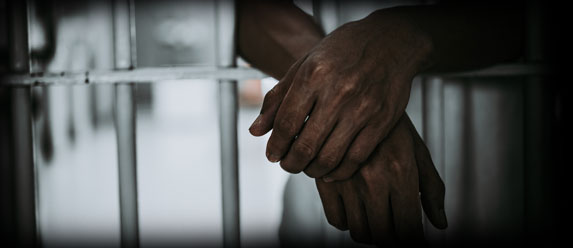 Image of jail cell showing a mans arms leaning outside of the bars.
