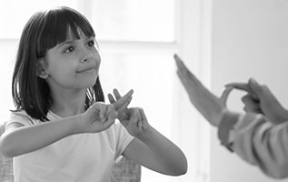 Photo of a young girl communicating in sign language to an adult.