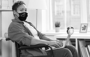 Photo of a woman with a disability in a wheelchair wearing a medical mask to prevent Covide-19