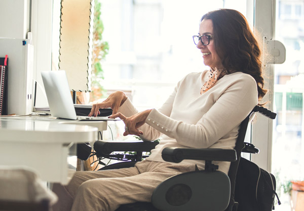 A woman with a disability working at her desk.