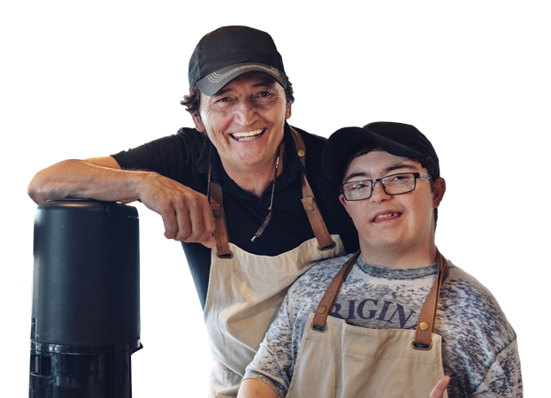 A photo of a developmentally disabled person next to his boss. They are at a bakery where they work.