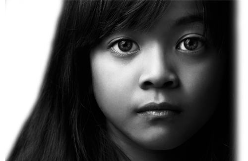 Closeup of the face of a young latino girl. She has a very sad look on her face.