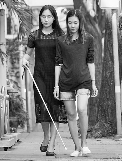 Photo of a blind woman with a walking cane walking on a sidewalk. She is being assisted by another woman.