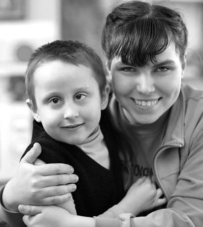 Photo of a woman hugging a young boy who has a mental disability.