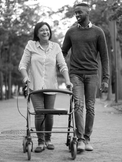 Photo of disabled woman in a walker. A man is next to her helping out. They are both enjoying a nice day at the park.