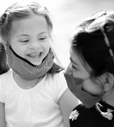 Photo of a woman hugging a young girl who has a mental disability. They both have medical masks on due to COVID-19