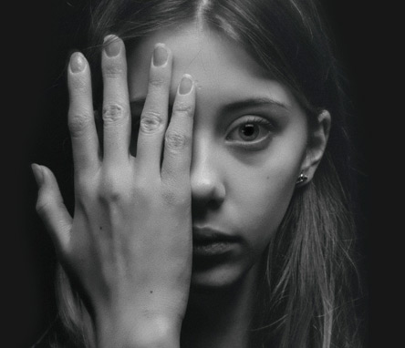 Close up image of a young woman's face who has a sad look. Her hand is covering half her face as she is directly looking at you.