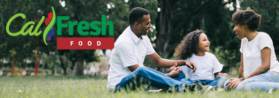 Photo of an African American family having a picnic. A mother and father are sitting looking at their daughter who sitting in between them. The CalFresh logo is overlayed on the image.