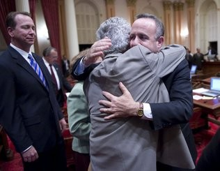 Photo of men in suits hugging after a victorious legal proceeding.