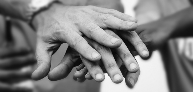 Close up image of a families hands layered on top of each other