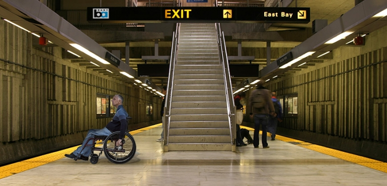 Photo of man in wheelchair waiting for a BART train at a station