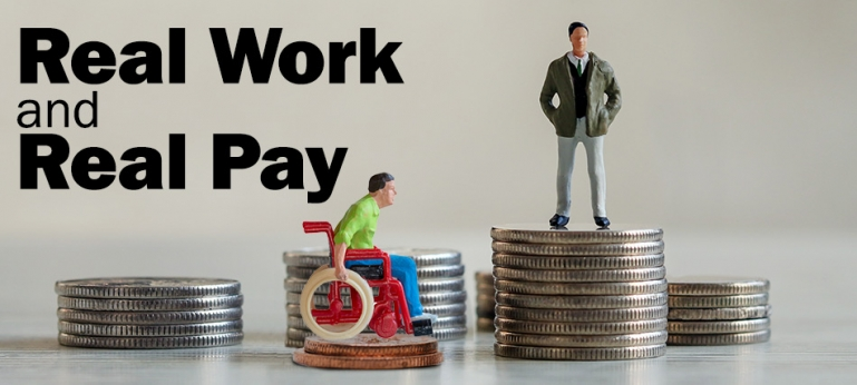 Real Work and Real Pay - Photo of photo of a figure of a man in a wheelchair on top of two pennies along side a figure of a business man on top a stack of qaurters