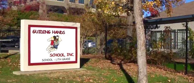 Image of the Guiding Hands School sign in front of the building
