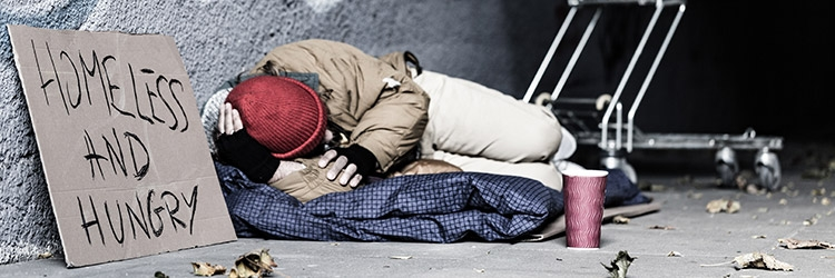Photo of a homeless man sleeping in a alley with a sign next to him with hand written words saying Homeless and Hungry.