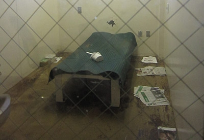 Inside of a dirty jail cell with garbage around bed.
