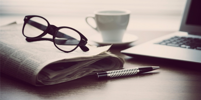 Image of a folder newspaper, eye glasses and a laptop sitting on a desk.