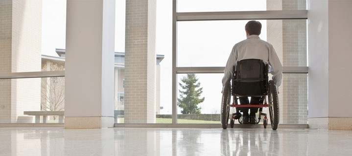 Man in wheelchair looking out window
