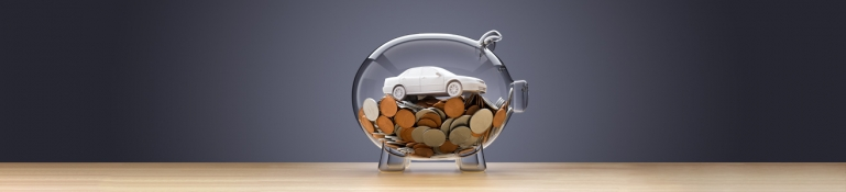 A piggy bank on a table with coins and a model car inside.