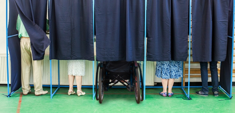 Image of legs of people behind a curtain at a voting boot. One of the voters is in a wheelchair