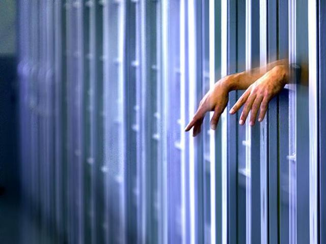 Photo of a set of hands poking out through jail bars.
