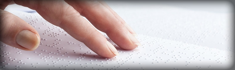 Closeup on the hand of a blind person reading a braille document