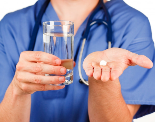 Stock photo of a nurse handing you a glass of water and meds.