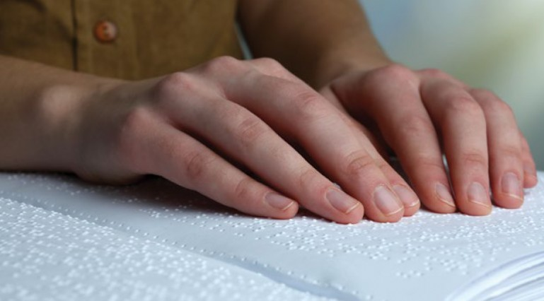 Close up photo of a person reading a braille document.