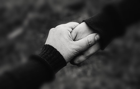 Close of of two hands holding each other in a caring way