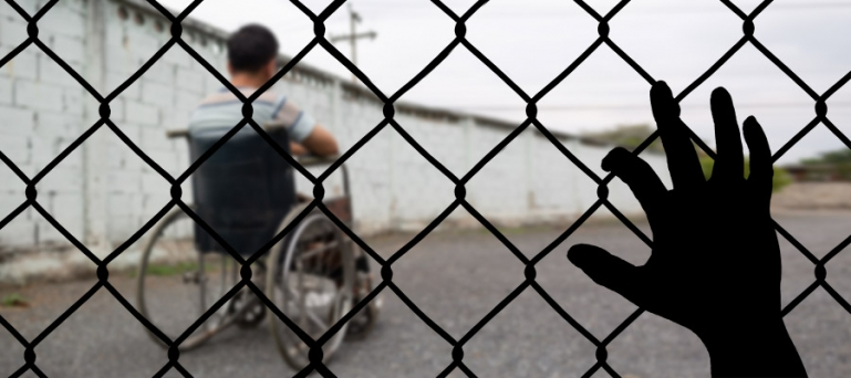 Photo of a disabled person behind a fence in a detention facility.