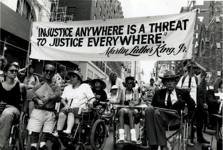 "Marchers in wheelchairs under a banner that reads ""Injustice anywhere is a threat to justice everywhere,"" Martin Luther King Jr."