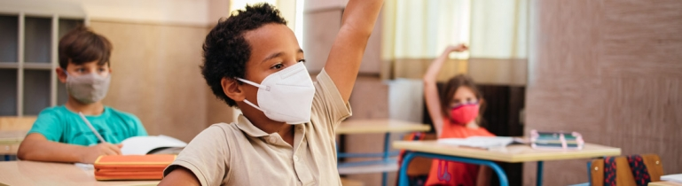 A little boy in a classroom wearing a medical mask to protect herself from COVID