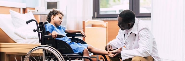 Photo of a young child in a wheelchair with a doctor kneeling down looking at his leg.