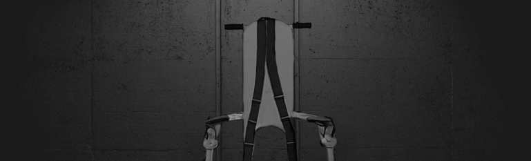 An image of a jail restraint chair in a dark room.