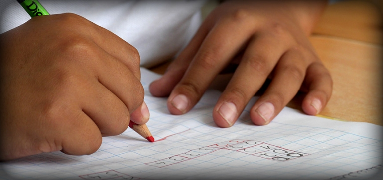 Photo of a close up of a little girls hands. She is solving a math problem on a piece of paper.