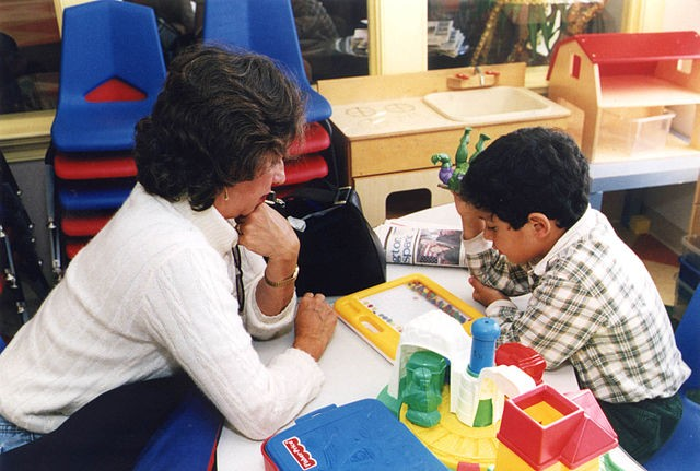Teacher helping young child in classroom