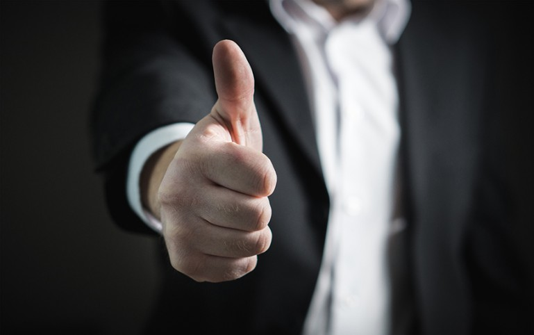 Person in business suit giving thumbs up.