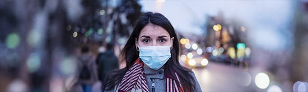 Photo of a lone woman in the street wearing a medical mask to prevent spread of germs.