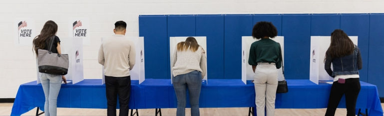 Several people at a voting booth