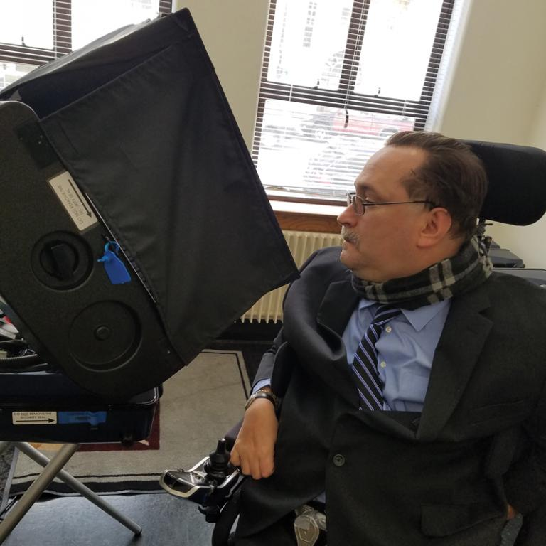 Photo of Fred Nisen inspecting an accessible voting station.