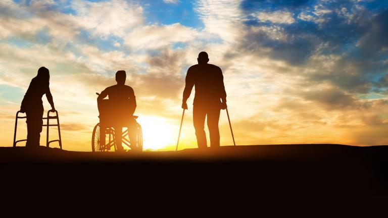 Photo of a three people with disabilities silhouetted against a sunset.