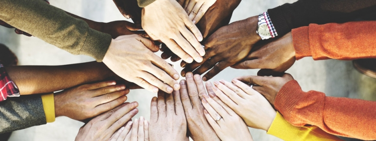 Photo of people of different races hands together in a circle.